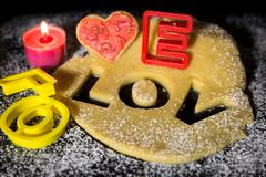 cookie dough, cookie cutter, black stone with icing sugar and a candle, conce - stock photo