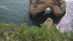 Boat goes through the hole in the rock Stock Footage