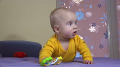 inquisitive baby girl play with toy rattle lie on sofa. 4K - stock footage