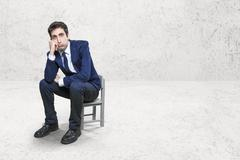 Portrait of bored businessman sitted on chair - stock photo