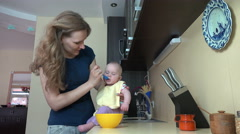 Stock Video Footage of Careless mother woman feed baby on table in kitchen. 4K