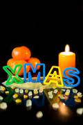 Cookie cutter building the word Xmas, tangerines and candle, black background - stock photo