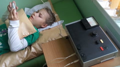 Little girl playing smartphone while laying sofa at elecrophoresis procedure Stock Footage