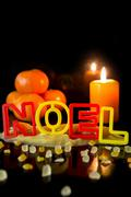 Cookie cutter building the word noel, tangerines and candle, black background - stock photo