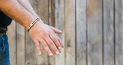 Arrest, close-up shot man's hands with handcuffs in front of plank wood wall - stock photo