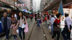 POV walk through street market in Hong Kong, many people mill around Stock Footage