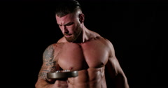 Portrait shot of a muscular man does bicep exercise with dumbbells in a gym. Sho Stock Footage