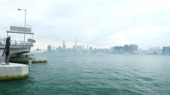 Cloudy harbour shore from opposite side, evening haze, white vessel on water Stock Footage