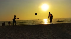 Video of a son and his father silhouette playing football on ocean beach suns Stock Footage