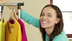 Young smiling woman pushing a movable rack of clothes, slow motion HD - stock footage