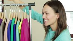 Young smiling woman pushing a movable rack of clothes, slow motion HD Stock Footage