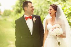 Beautiful bride and groom with bouquet on wedding day - stock photo