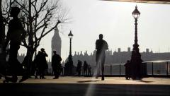 LONDON, UK - FEBRUARY 19, 2013: Tourists walk along the Thames south bank Stock Footage