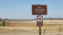 Dry Folsom Lake No Lifeguard On Duty sign (pan) - stock footage