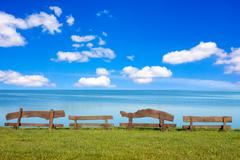 Wooden benches in front of the sea Stock Photos