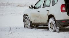 SUV car standing in a snowy field in winter Stock Footage