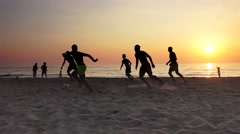 Video of a son and his father silhouette playing football on ocean beach suns - stock footage