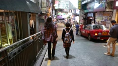 Two Asian girlfriends walk down night street, chase camera follow behind - stock footage