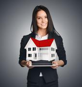 Business woman showing house symbolizing sale of real estate Stock Photos
