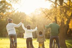 Rear view of a young family with arms raised on bike Stock Photos
