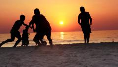 4k Silhouette of three guys playing football on the beach at sunset Stock Footage
