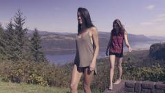 Two Young Women Balance/Walk On Rock Wall At A Scenic Overlook In Oregon (4K) Stock Footage