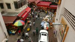 People fuss around street, market stalls around building corner, time lapse shot Stock Footage