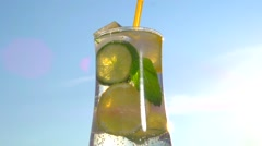 Cocktail. A glass with ice and fruit on the background of the sky. - stock footage