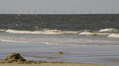 Beach at North Sea with wind turbines woman and child - stock footage