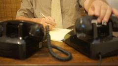 Office clerk - man answers two old black telephones continuously writing notes Stock Footage