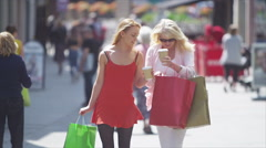 Attractive smiling mother & daughter walking through busy shopping area - stock footage