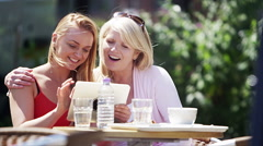 Attractive smiling mother & daughter looking at computer tablet outdoors Stock Footage