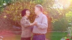 Senior Couple Dancing In A Garden Stock Footage