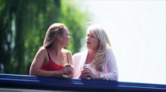 Attractive mother & daughter having heart to heart conversation outdoors Stock Footage