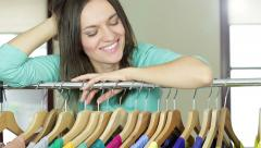 Portrait of beautiful young smiling woman near rack with hangers HD Stock Footage