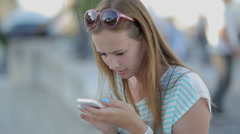 Girl seriously using a smart phone in a city embankment sitting Stock Footage