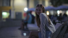 Beautiful girl sitting on a bench at embankment in the evening smiling and Stock Footage