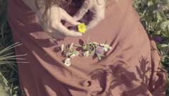 Closeup Of Woman's Hands As She Arranges Wild Flowers In Her Dress, In A Field Stock Footage