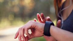Young woman jogging with stopwatch in the forest - stock footage