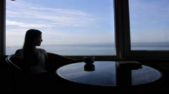 Long shot of silhouette of young beautiful girl sits in a cafe with panoramic Stock Footage