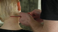 Hairdresser trimming blond hair with scissors Stock Footage