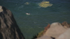 Small boat at the foot of rocks and cliffs at Cabo da Roca Portugal, stormy Stock Footage