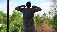 Young handsome man stretching arm, enjoying day on terrace, shot at 240fps HD Stock Footage