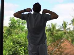Young handsome man stretching arm, enjoying day on terrace, shot at 240fps NTSC Stock Footage