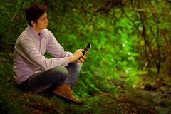 Young handsome man using tablet outdoors with great internet connectivity in the - stock photo