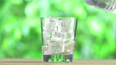 Water Bottle and Glass Of Ice Cubes on Wood Table Stock Footage