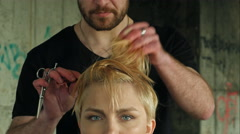 The master does a hairdress to a blond girl - stock footage