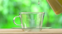 Aromatic tea pouring into glass cup on the on nature background. Stock Footage