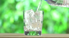 Bottle and Glass of Water on wood table on summer background Stock Footage