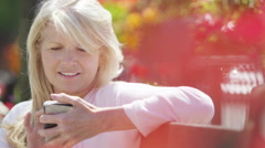 4K Portrait of beautiful mature woman looking at mobile phone outdoors in city Stock Footage